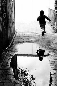 Henri Cartier-Bresson. In this photo I like how the reflection in the puddle is so clear, the water is like glass. I also like how you can not see past the person. It is bright so gives you an image in your head and seems weird.:
