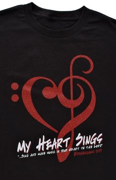 """Rejoice in the Lord with this black short sleeved T-shirt, featuring a stylized red heart and musical clef image decorated with musical notes. Music is a wonderful way to praise Him, and this shirt declares that """"My Heart Sings"""" for the Lord. The Scripture below reads, """"...sing and make music in your heart to the Lord."""" - Ephesians 5:19"""