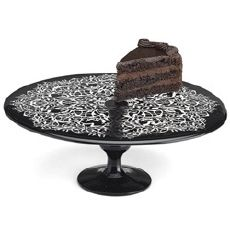 Slice of multilayered chocolate, mousse and fudge cake with fondant icing on black lace designed platter