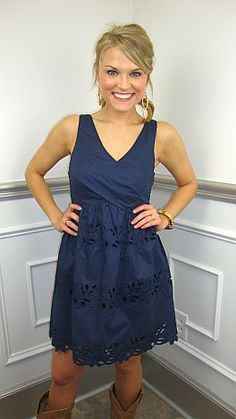 Tailored through the torso with an A-line bottom... this is a fit that will never do your wrong! This navy blue dress is 100% cotton and adorned with eyelet cutouts across the skirt. With cowboy boots, it's your perfect concert or gameday outfit. With pumps or flats, it becomes your Easter dress! (Fully-lined with side zip.)