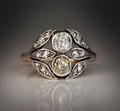 A Belle Epoque Diamond Diadem Ring, Circa 1890. A stylish silver-topped gold ring vertically set with two old mine cut diamonds, one bright white diamond and one light greenish-yellow diamond flanked by six leaves embellished with rose cut diamonds.