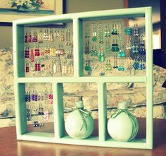 Spray paint a wooden shadow box, adhere chicken wire netting with staples, and add jewelry!