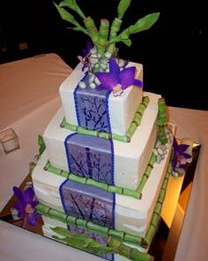 three tier asian style white and purple square cake with green bamboo & decorated with purple orchids and stone pebbles
