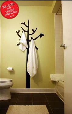 Não quer ter que furar a parede para instalar suportes para toalhas? Nessa sugestão, um adesivo de parede em formato de árvore e alguns suportes com ventosas criaram um ar descontraído dentro do banheiro.