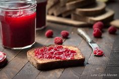 A toasted slice of low carb bread slathered in sugar free raspberry jam on a dark brown lath wood surface with an opened jar of jelly to the left, a silver knife with jelly to the right and sliced bread on a wooden handled cutting board in the background.