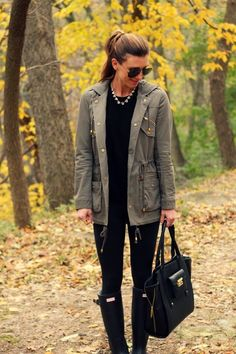 black sweater black skinny jeans green army jacket rain boots chunky jeweled necklace large black purse