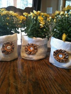 my own design for fall mum plant bags: a simple bag sewn from white burlap, add a fall color yo-yo, felt circle and button.  I think they came out cute : )