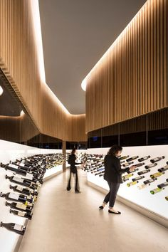 "Bottle display. |  Feature lighting. |  Designed by local architect Arthur Casas it is a perfect example of how to make a boring, long space look magnificent. We like the bottle display system that shows each bottle label-up, and eliminates the need to handle the bottles. The long ""selection hall"" leads to a bar area, designed for learning about wine by reading and tasting."