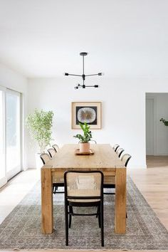Wooden dining table + mid century style light fixture | Carly Waters Style