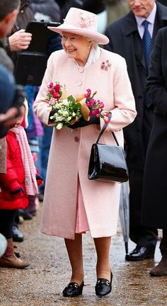 Queen Elizabeth II receives flowers from members of the public during a walkabout after attending Sunday service at the church of St Peter and St Paul in West Newton on 01.02.2015 near King's Lynn, England.