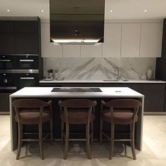 Kitchen at the apartment project- we replaced the glass splashback for calacatta oro bookmatched marble, clad the extractor in bronze mirror...