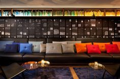Amsterdam's Ink Hotel occupies the former offices and print shop of Dutch newspaper De Tijd, and Concrete Architects was inspired by the space's history. The library walls display historic newspapers, and a suspended shelf holds books arranged in a colorful gradient.