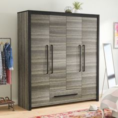 An excellent addition to your master suite, entryway, or spare room, this substantial four-door, one-drawer armoire lends curated contemporary style to your ensemble. Made from natural wood with manufactured wood components, this attractive design strikes a tall rectangular silhouette finished in an oak gray veneer with a scratch-resistant melamine coating and chunky black metal hardware. Four doors open to two separate cabinet spaces with shelving for everything from sweaters and chinos to…