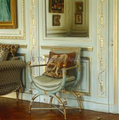 In the main salon a painted and gilded Empire armchair exactly matches the eau de nil of the panelling behind and is accompanied by a cushion depicting a British bulldog