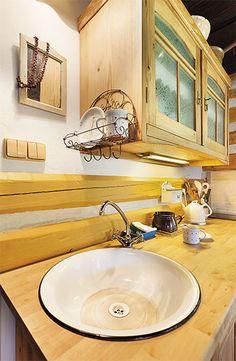 Do pracovní desky je zapuštěno obyčejné smaltované umyvadlo. Na velké vaření kuchyň připravena není, ale nevadí to, stačí trocha kuchařské kreativity