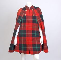 Wool Tartan plaid cape from the mid 1960s. It features tartan plaid fabric throughout, four decorative gold crest buttons, with a metal center, Queen of Capes Country Place for B. Altman & Co.