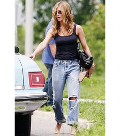Our Favorite Denim Moments Throughout The Years via @WhoWhatWear - Jennifer Aniston Off the clock, Aniston keeps it cool and classic in slouchy Levi's jeans and a fitted tank.