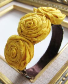 rolled flower bracelet. Site has a tutorial including video on how to make these rolled flowers out of fabric. Also has 11 other projects you can do using these.