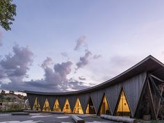 the building features a swooping roofline, which descends at its center to demarcate its entrance.
