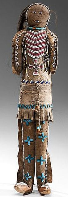 Arapaho Beaded Hide Warrior Doll, thread and sinew-sewn attenuated hide doll dressed in traditional moccasins, leggings are detailed with four light blue crosses, and his a long tunic shirt is decorated with a thunderbird and cross on back. A red white-heart beaded breastplate with Maltese Cross, representative of the protection of the Morning Star, is situated on his chest, height 17 in. fourth quarter 19th century