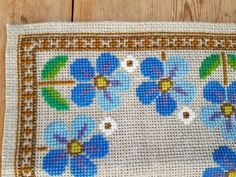 Beautiful blue floral cross stitch embroidered tablecloth in mint condition. Spotless. The size is: 11 3/4 x 11 3/4  The material is linen, cottonthread, woolyarn. I allso offer combined shipping and refund if the shipping cost is overpaid.  Contact me if you have questions  Thank you for visit my vintage shop :)