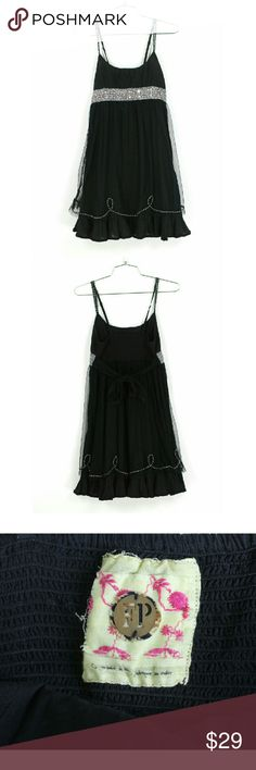 """Free People black party dress Size 0. Free People black party dress. Features a smocked back, adjustable spaghetti straps and beaded embellishments. Polka-dot mesh overlay with tiered ruffled hem.  Ties in the back.  Cotton/nylon. Excellent condition, no flaws. Approximate measurements Bust 27"""" Length  32"""" Waist unstretched 24"""" . Free People Dresses"""