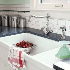 Easy-care surfaces including ceramic tile, engineered quartz and a vintage-style faucet with just a single stem to clean around make this a family-centric kitchen that can take hard knocks.   Photo: John Granen   thisoldhouse.com