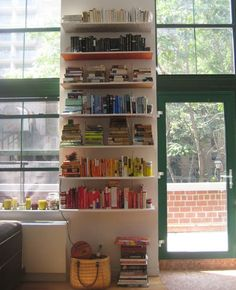 "As if our obsession with owning books weren't enough to deal with on its own, we've now also become obsessed with the ""bookcase of the day"" feature on Jamie Meares' blog, I Suwannee. The book storage solutions she posts are always fun to admire, but the one that greeted us at the start of this week was especially charming. From this angle, Ariel's shelves look great, but fairly ordinary, right? Just click through to view the DIY surprise that makes these shelves special..."