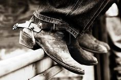 Rodeo cowboys' experienced boots & spurs on an iron rail