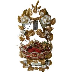 A French marriage crown cushion with red velvet cushion surrounded by gilt metal leaves and flower heads with ceramic flower heads around the three