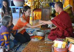 Monk in Vientiance presenting string bracelet to girl. Good luck in endeavours. For more on Buddhist Monk Blessing Ceremony for Sai Sin Sacred thread bracelets (string bracelets) in Thailand, Nang Rong, Buriram area of Eastern Thailand (isan), Southeast Asia check here. http://live-less-ordinary.com/southeast-asia-travel/buddhist-monk-blessing-ceremony-thailand