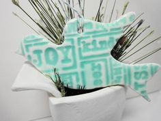 """This ornament is made of stoneware clay and hand-decorated.    It is glazed in aqua.    Finished with white and aqua bakers twine.    Dimensions are 3 3/4"""" x 2"""" approximately."""