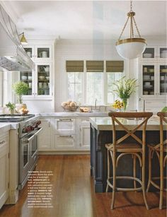 Brass light fixture, white kitchen, painted island, wood natural accents.
