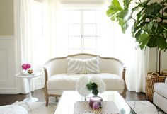 White living room with slight pattern on pillow and pink flowers in white vase