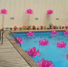 Flowers in pool but candles lined by pool with flowers too