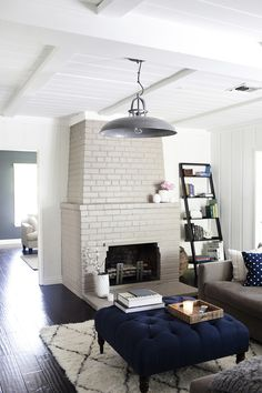 Neutrals and navy. Living room with dark hand scraped wood floors, white beamed ceilings
