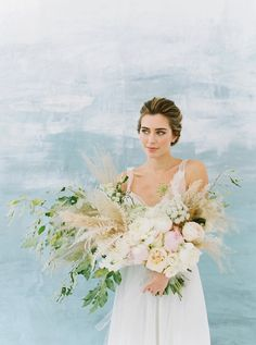 Overflowing wedding bouquet filled with pampas grass and peonies