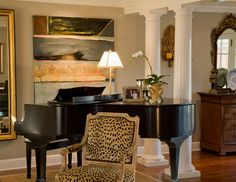 Dark Black Piano / Louis Style Chair upholstered with leopard faux-fabric ; set in a Traditional-Living Room parted from dining space by a double row of white tuscan columns.