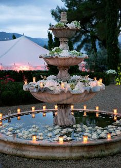 4. Floral fountain: If your venue has a fountain, floating florals are a must. We love a cascading look that drips down each tier of the water feature.