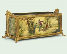 A FRENCH ORMOLU AND CERAMIC PANELLED JARDINIERE CIRCA 1890 with gargoyle mask handles and scroll feet, the ceramic panelled sides finely painted with courtly figures in romantic landscapes, signed twice Ed. Tourteau 12¼ in. (31 cm.) high; 29½ in. (75 cm.) wide; 10 in. (25.5 cm.) deep