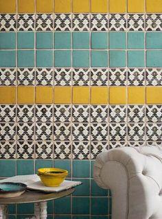 Patterned tiles in teal, yellow, black and white.
