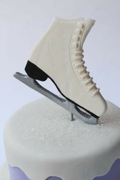 Close up of gumpaste skate on ice skating cake.  Glitter snow, purple fondant.  Made by Cakes by Caralin.  www.cakesbycaralin.com