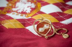 http://www.culturaltravelguide.com/how-to-plan-your-trip Harry Potter, Hermione's Time Turner keychain. See the Gryffindor crest behind? Photo: www.fotosmatrimoniobogota.com #harrypotter #jkrowling #Gryffindor #timeturner #Hermione