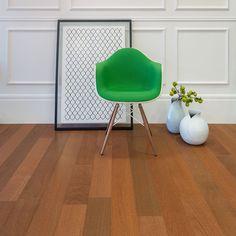 Piso de madeira, cadeira verde e vasos brancos.