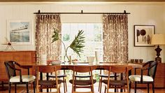 Brown-hued dining room with retro chairs and patterned rug sits infront of large windows with brown patterned-drapes