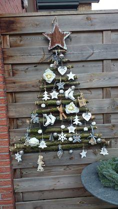 Kerstboom van takken uit het bos. Aan elkaar geknoopt met binddraad. Versiering met ledlampjes en allerlei kerstartikelen.