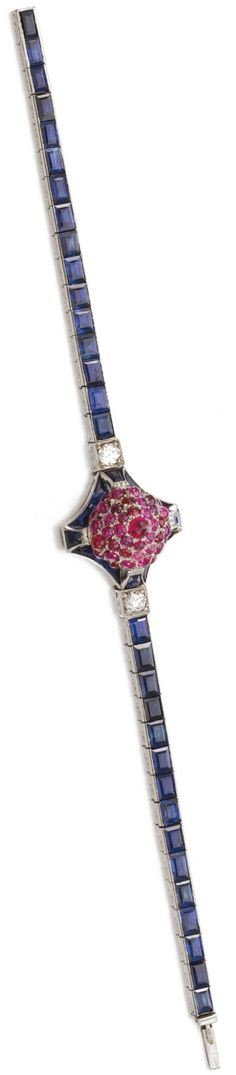 An Art Deco ruby, sapphire and diamond bracelet, 1920s. The central element set with a cluster of cabochon and circular-cut rubies, to a line of calibré-cut sapphires and circular-cut diamonds. #ArtDeco #bracelet