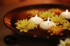 shallow bowl with floating flowers and candles