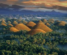 "These conical limestone mounds are covered in grass that turns brown in the dry season, giving the hills their ""chocolate"" moniker. Over 1,000 such formations exist in Bohol province, standing 100 to 300 feet tall."