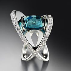 XOX Tourmaline Ring by Adam Neeley.  XOX Tourmaline Ring features classical elements with bold sculptural lines. This unique ring design features a dazzling blue-green (indicolite) tourmaline with diamond accents set in white gold.
